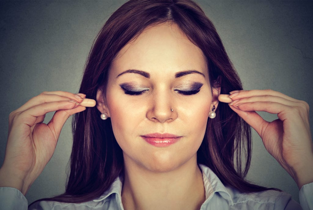 Kvinne med ørepropper med lydkansellering fra HØR.