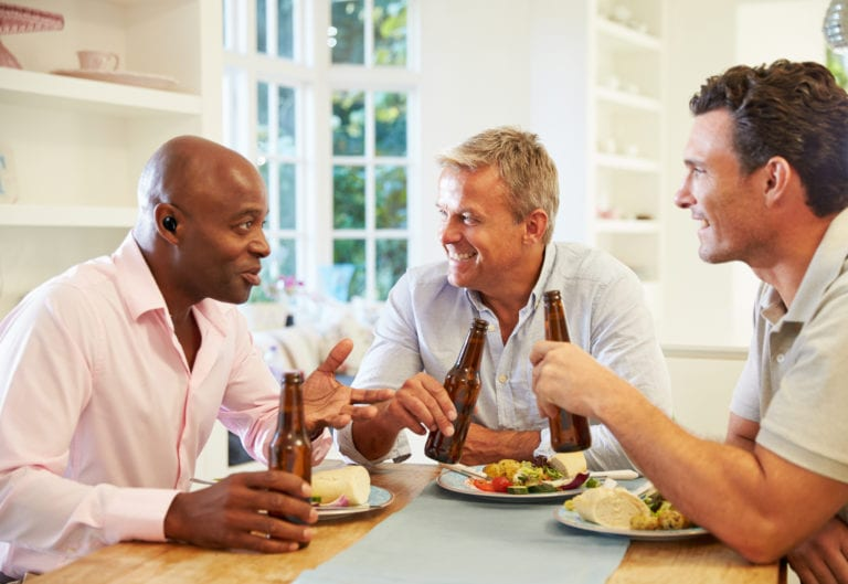 Mature Male Friends Sit At Table Drinking Beer And Eating