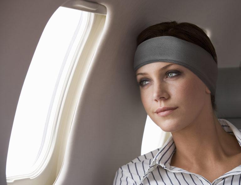 A businesswoman listening to music on a flight